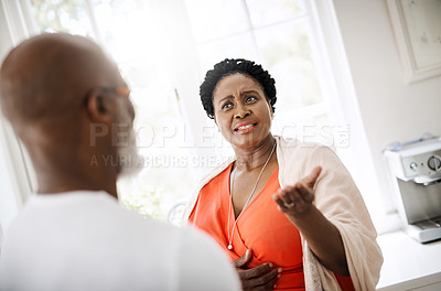 Buy stock photo Shot of a mature couple having a serious conversation at home