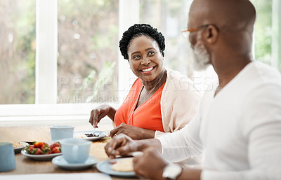 Buy stock photo Shot of a happy mature couple enjoying a relaxing breakfast together at home