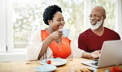 Buy stock photo Shot of a happy mature couple using a laptop while having breakfast together at home