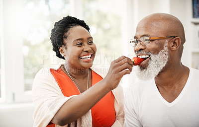 Buy stock photo Shot of a happy mature woman lovingly feeding her husband a strawberry at home