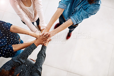 Buy stock photo High angle shot of a group of young businesspeople joining hands in solidarity in a modern office