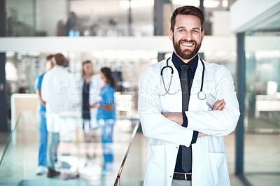 Buy stock photo Cropped portrait of a handsome male doctor standing with his arms folded in the hospital