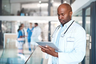 Buy stock photo Cropped shot of a handsome male doctor using his tablet while standing in the hospital
