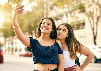 Buy stock photo Cropped shot of two best friends taking a selfie in the city