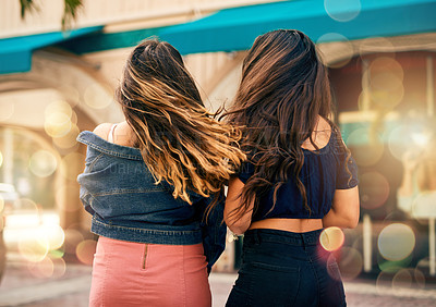 Buy stock photo Rearview shot of two unrecognizable female best friends hanging out together in the city