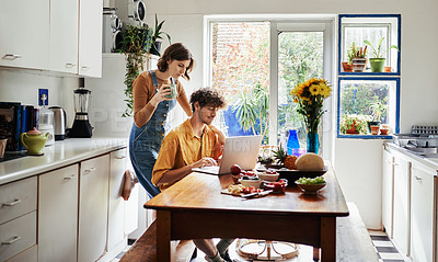 Buy stock photo Shot of a young man using his laptop while spending time at home with his girlfriend