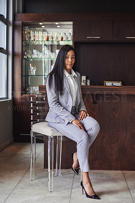 Buy stock photo Portrait of a young businesswoman sitting on a chair in a bar