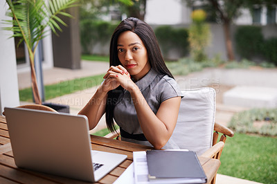 Buy stock photo Portrait of an ambitious young businesswoman using a laptop at a table outdoors