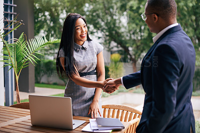 Buy stock photo Shot of a young businesswoman and businessman shaking hands outdoors