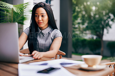 Buy stock photo Shot of an ambitious young businesswoman using a laptop at a table outdoors