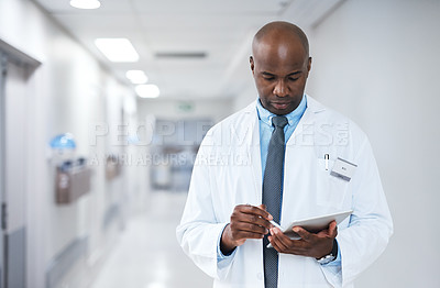 Buy stock photo Cropped shot of a handsome mature male doctor using a tablet while working in the hospital