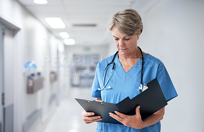 Buy stock photo Cropped shot of a mature female nurse going through medical records while working in the hospital