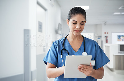 Buy stock photo Cropped shot of an attractive young female nurse using a tablet while working in the hospital