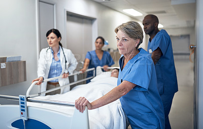 Buy stock photo Shot of doctorsCropped shot of a medical team pushing a patient down the hallway in a gurney in a hospital