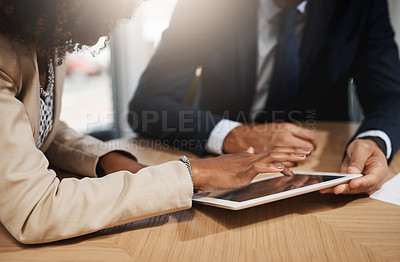 Buy stock photo Closeup shot of two unrecognizable businesspeople using a digital tablet in an office