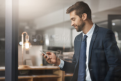 Buy stock photo Shot of a young businessman using a cellphone while working late in an office