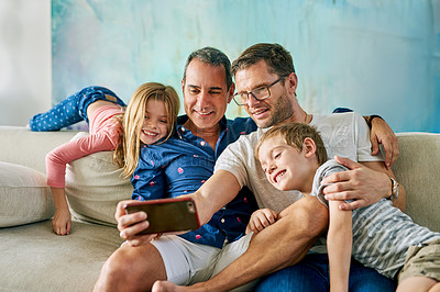 Buy stock photo Cropped shot of an affectionate family of four taking selfies on the sofa at home