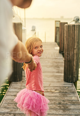Buy stock photo Cropped shot of an adorable little girl leading her father down the pier at the beach