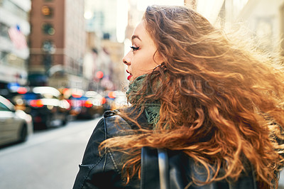 Buy stock photo Rearview shot of a young woman out in the city