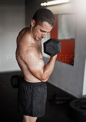 Buy stock photo Cropped shot of a handsome and muscular young man working out with a dumbbell in the gym