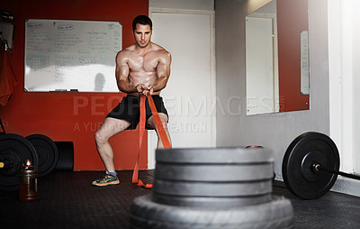 Buy stock photo Full length shot of a handsome and muscular young man pulling weights in the gym