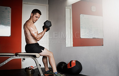 Buy stock photo Full length shot of a handsome and muscular young man working out with a dumbbell in the gym