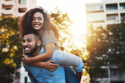 Buy stock photo Cropped shot of a young handsome man giving his girlfriend a piggyback ride outside in a public park