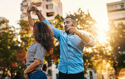 Buy stock photo Shot of a happy young couple dancing in the park