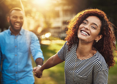 Buy stock photo Portrait of a happy young couple holding hands in the park