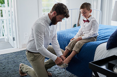 Buy stock photo Cropped shot of a young handsome father helping his adorable son put on his shoes at home