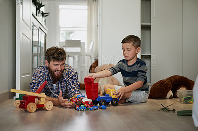 Buy stock photo Shot of a handsome young man and his son playing with toys on the bedroom floor