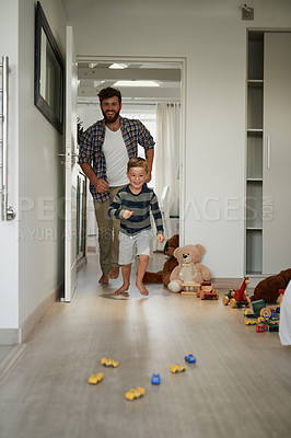 Buy stock photo Full length shot of a handsome young man chasing his son around the house