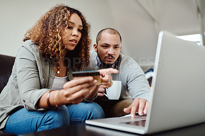 Buy stock photo Shot of a young couple using a credit card and laptop at home