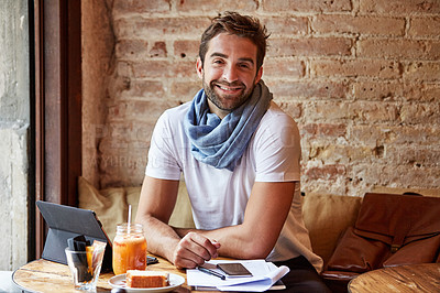 Buy stock photo Cropped shot of a handsome young man sitting in a coffee shop