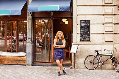 Buy stock photo Shot of a young woman standing in front of her coffee shop