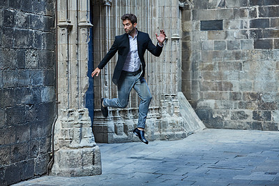 Buy stock photo Full length shot of a handsome young businessman leaping through an urban alleyway