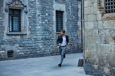 Buy stock photo Full length shot of a handsome young businessman running through an urban alleyway