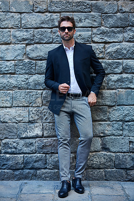 Buy stock photo Full length portrait of a handsome young businessman standing against a brick wall in an urban alleyway