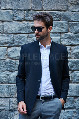 Buy stock photo Cropped shot of a handsome young businessman standing against a brick wall in an urban alleyway