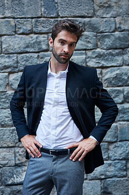 Buy stock photo Cropped portrait of a handsome young businessman standing against a brick wall in an urban alleyway