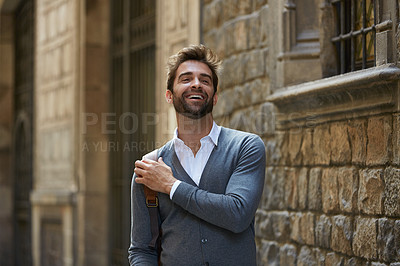 Buy stock photo Cropped shot of a handsome young businessman laughing while walking through an urban alleyway