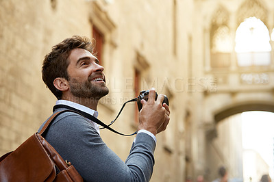 Buy stock photo Cropped shot of a handsome young businessman taking photographs while overseas on a business trip