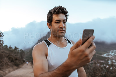 Buy stock photo Cropped shot of a handsome young man checking his cellphone while running in the mountains