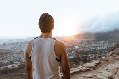 Buy stock photo Rearview shot of an unrecognizable young man taking in the views while running in the mountains