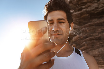 Buy stock photo Cropped shot of a handsome young man listening to music while out for a run in the mountains