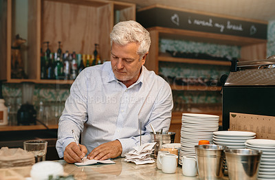 Buy stock photo Cropped shot of a mature male entrepreneur writing down orders while standing in his self-owned coffee shop