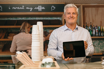Buy stock photo Cropped portrait of a mature male entrepreneur showing you a tablet screen while standing in his self-owned coffee shop
