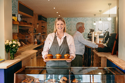 Buy stock photo Cropped portrait of a mature female entrepreneur carrying a tray of muffins while working in her self-owned coffee shop