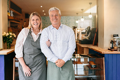 Buy stock photo Cropped portrait of a mature couple standing arm in arm in their self-owned coffee shop