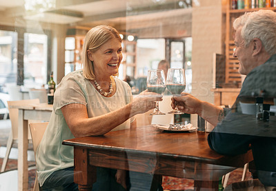 Buy stock photo Cropped shot of an affectionate mature couple toasting while enjoying their date in a coffee shop
